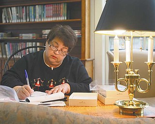 """Mary Jo DeLucia of Austintown has sent thousands of Christmas cards with hand-written notes to Marines in combat zones since beginning the project in 2004. Here she signs and packs cards to be sent this year. DeLucia says she does the project at the Poland Branch of the Public Library of Youngstown and Mahoning County """"because it is so peaceful there."""""""