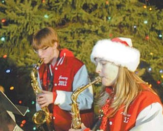 Austintown Fitch High School band members Jeremy Eyster and Amanda Lacusky play Christmas carols before the 25th annual Christmas-tree lighting at Wickliff e Circle Fire Station in Austintown. Several hundred residents enjoyed music, cookies and a visit from Santa on Thursday evening.
