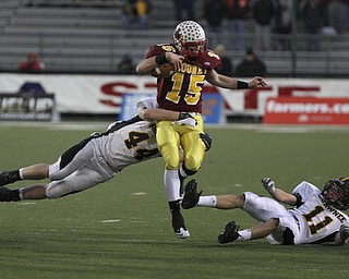 Mooneys #15 breaks through the line as #11 Grant Miller and #44 Ryan Mayfield hang on. Youngstown Cardinal Mooney won their 8th championship as they beat the Shawnee Braves in Fawcett Stadium  21-14. (AP Photo/The Vindicator, Robert K. Yosay)