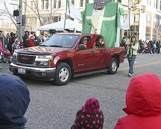 JESSICA M. KANALAS | THE VINDICATOR..Children loon on as the St. Patrick's Church display drives by during the holiday parade in Downtown Youngstown.