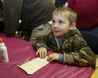 JESSICA M. KANALAS | THE VINDICATOR..Richard Yaist, 6, of Youngstown makes an ornament out of musical paper at the YSU SMARTS table which had several craft activities  during the entire holiday event in Downtown Youngstown.