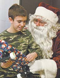 Jacob Burkett, 10, of East Canton, visits Santa at the party for family members of deployed Army National Guard soldiers in Lordstown.