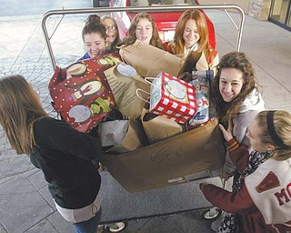 Girls from the Boardman Poland Junior Women's League Juniorettes program help load gifts for senior citizens. Volunteers wrapped the gifts at the Holiday Inn in Boardman on Thursday as part of a program called Be a Santa to a Senior, sponsored by Home Instead Senior Care of Austintown.