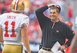 San Francisco head coach Jim Harbaugh grimaces after his offense fails to move the ball as Alex Smith comes off the field during the second quarter of Sunday's game against Arizona in Glendale, Ariz.