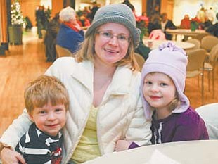 Jan Billock sits with her children, 4-year-old Hayden, left, and 5-year-old Dylan at the Merry Bright Nights event at Fellows Riverside Gardens in Mill Creek Park.
