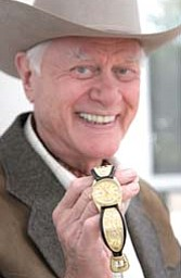 """Actor Larry Hagman shows off a wrist watch elaborately decorated with the initials """"J.R"""" inscribed on the bands."""