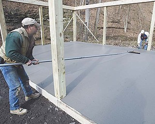 Paolo Ricottilli, left, and his brother, Lee, put the finishing touches on a concrete pad that will be the floor of the new Lowellville School District science lab in Pine Hollow Park. The brothers own Ricottilli Construction of Poland Township.