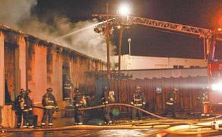 Youngstown firefighters used two ladder trucks to pour water onto the roof of the Omega Door Co.