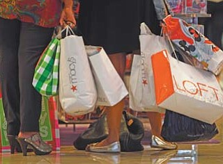 Shoppers stop to look at a display at Dadeland Mall in Miami. Americans spent more on autos, furniture and clothing last month as retail sales rose for the sixth-straight month.