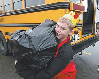 Sixth-grader Danny Moore, a Crestview student, takes a bag from the Springfield bus during the two schools' annual holiday project.