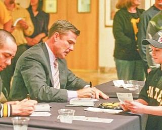 Pittsburgh Pirates pitcher Jeff Karstens, left, and team president Frank Coonelly sign autographs for Ramsey Brown, 7, of Sharon, Pa., at the annual Pirates Caravan event Wednesday at The Butler Institute of American Art in Youngstown. Normally reserved for the end of January, the annual event was moved up a month because the team was itching to get the season going, said Coonelly.