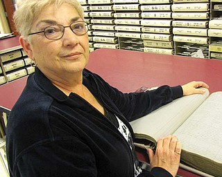 Diana Marchese, Trumbull County recorder, stands with a 100-year-old index book for property deeds at the recorder's office. The book is an example of the good condition they are in now, and Marchese hopes they will stay that way. But she expects the title searchers who use them to increase in number in the weeks to come, as about 80,000 Trumbull County acres are leased at once for shale drilling.