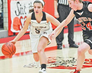 McKenna Shives (5) of Struthers dribbles around Canfi eld defender Rachel Tinkey (24) while on her way to the basket during an All-American Conference basketball game Thursday at Struthers Fieldhouse. The Wildcats defeated the Cardinals, 54-48.