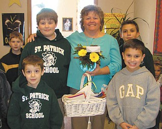 """Principal surprised: St. Patrick School in Hubbard celebrated Principal's Day recently by surprising Cindy Lacko, the school's principal. Students and staff assembled after lunch outside her office to watch cheerleaders perform the """"Lacko Rumble"""" and other cheers. Afterward, Lacko was presented with a flower arrangement and handcrafted cards by each grade. Some of the students are, left to right, front row: Sam Wirtz and Joe Madeline; middle row: Daniel Robinson and Lacko; and back row: Ian Smith and Nick Matisi."""