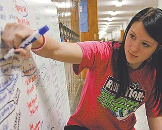 Morgan Leonard, 13, an eighth-grader, crosses a toy off the board Friday at Canfield Middle School. She was working on the Leo Club's Operation Christmas Carol, which collects toys for needy children throughout the Canfield area. The Leo Club is a student affiliate of the Lions Club. Members of the club earned money to help buy presents for children.