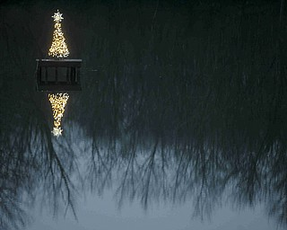 JESSICA M. KANALAS | THE VINDICATOR Frank and Paula Dietz also place a 4-foot tree on a platform in the middle of a lake in the backyard of their Springfield Township home. Frank gets the tree to its location by paddle boat, while Paula watches from their deck to make sure it's standing straight. The lights operate on a timer.