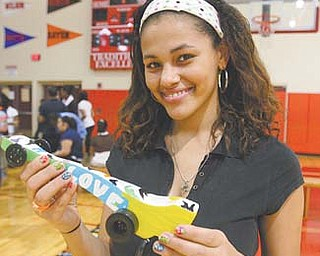 Drucella Garcia, a junior at Chaney's Science, Technology, Engineering and Math School, shows off the dragster  she designed, built, sanded and painted to race in the school gymnasium.