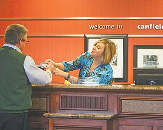Elizabeth Caman, assistant general manager at Hampton Inn & Suites in Canfield, helps Phil Gaulin of Buffalo, N.Y. Local hotels have had higher occupancy rates this year, partially due to those coming here involved in the Utica and Marcellus shale-drilling activity.