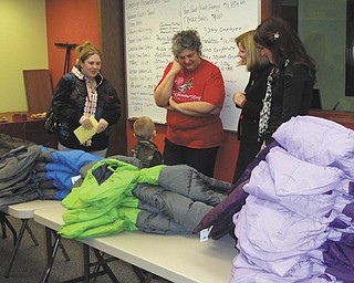 Salvation Army caseworker Marta Nagel, center, along with PNC Bank employees Debbie McMaster and Candace Turpack, right, help a young boy pick out a brand-new winter coat while his mother looks on. The coat distribution was made possible through the PNC Foundation, United Way of Mercer County and Operation Warm, whose sole mission is to provide new winter coats to children in need.