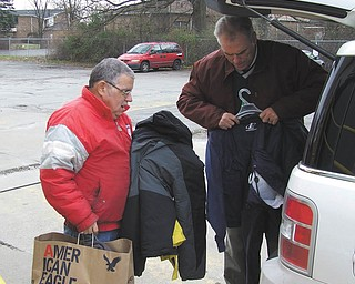 """Members of the Youngstown Lions Club recently donated gently worn coats to Goodwill Industries. Club member Doug Lewis, right, is feeling a little like """"Santa"""" as he makes a delivery to Tom Sullivan. The Lions club meets every Thursday at noon at the Youngstown Club on East Commerce Street. For membership information contact them at P.O. Box 1262, Youngstown, OH 44501, or check them out on Facebook."""