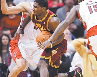 Cleveland Cavaliers' Kyrie Irving tries to get past Toronto Raptors' Jose Calderon, back, and Amir Johnson (15) during the first quarter of their NBA game Monday at Quicken Loans Arena in Cleveland. Irving, the No. 1 overall draft pick out of Duke, scored only six points in his NBA debut as the Cavaliers fell 104-96.