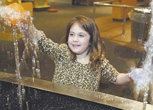 Katie Toepfer, 6, of Howland, tries to place a plastic ball on a stream of water at OH WOW! She was one of more than 150 visitors to the children's science center and Youngstown Business Incubator during the first Y-Town Tech Tour on Monday.