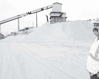 R.W. Sidley Co. owner Rob Sidley stands in front of a pile of crushed, rare conglomerate silica sand that can be processed into a wide variety of products including silica sand used to frack wells.
