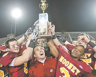 Members of the Cardinal Mooney football team, including (from left) seniors Cameron DiVito, Joe Deniro (6), coach P.J. Fecko and Roosevelt Griffin (3) hold the Division III state championship trophy following the Cardinals' 21-14 win over Springfield Shawnee at Fawcett Stadium in Canton.