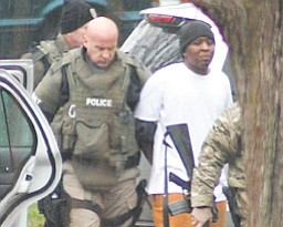 A SWAT team member leads Kevon Williams, 20, out of his Ohio Avenue home after a lengthy standoff with police.