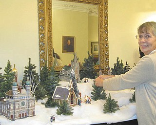 Patricia Burges-Fisher, a docent with the Niles Historical Society, makes final adjustments to the Christmas decorations at the Ward-Thomas Museum, 503 Brown St., Niles. The museum will be open for a final viewing on New Year's Day from 2 to 5 p.m. Department 56 houses and toys are mingled among old tree decorations and many other items. The President's Ladies gowns are displayed throughout the museum. For more information call 330-544-2143.
