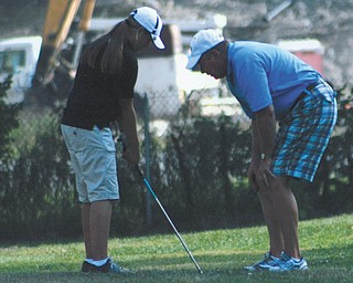 Haleigh Guerrero gets advice from Coach Hutchison at Avalon South Golf Course.
