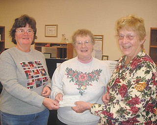 Roberta Lawrentz, center, of Girard Junior Womens League, presents donations to Sister Midge, left, and Sister Marjorie of Emmanuel Care Center. The center is dedicated to providing for needy families in Girard. Four-hundred bags of food and IGA gift certificates were donated at Thanksgiving, and the center plans to give 600 gifts at Christmas to qualifying families. Girard Junior Women is a nonprofit group; new members are welcome.