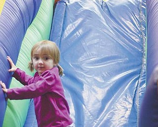 Lauren Ross, 5, of Canfield, at top, and Olivia Truby, 2, of Texas, play on a slide that is part of an obstacle course at Austintown Bounce on Kirk Road. Many children are taking advantage of the holiday school break to play this week at the indoor facility and other kid-friendly businesses in the Mahoning Valley.