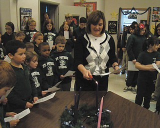 Students at St. Patrick School in Hubbard continued a tradition with a weekly Advent service to get ready for the birth of Jesus on Christmas Day. Each week a different class read short prayers, and songs were performed by all of the students to close the service. Above, fourth-grade teacher Joann Matune lights the Advent wreath.