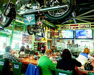 Patrons enjoy drinks and wings at the bar inside the new Quaker Steak and Lube in Boardman. The establishment, which moved from Market Street to its new site last August, was one of eight locations to open in 2011. The Sharon, Pa.-based business looks to open another 12 restaurants this year.
