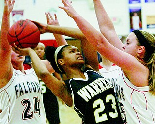 Fitch's Maura Bianco (24) and and Cassie Custer, right, try to shut down Harding's Audreyanna Baldridge (23) during the first half of a basketball game Monday at Austintown Fitch High School. The Raiders dominated the Falcons, 72-42.