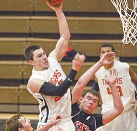 Howland's Chris Maze goes for two points past Struthers' Jake Jacubec, left, and Dylan Schmidt during first half action Tuesday at Howland.