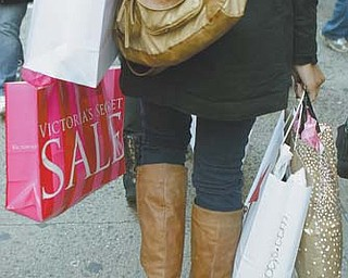 A woman walks down 34th Street carrying the fruits of her shopping expedition on the day after Christmas in New York. A flurry of post-Christmas bargain-shopping helped drive sales higher in the last week of December, according to a report Wednesday from a shopping-mall trade group.