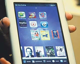 In this photo provided by Barnes & Noble, a demonstrator holds the new Nook Tablet in New York. Barnes & Noble said Thursday it is reviewing its options for its growing Nook e-book reader business and might spin it off from its core bookstore business.