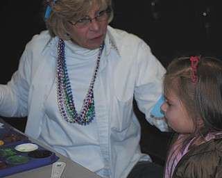 During First Night Canfield, the city's New Year's Eve celebration, Patty Cervello, left, prepares to paint the face of little Olivia Madura at Canfield Middle School.