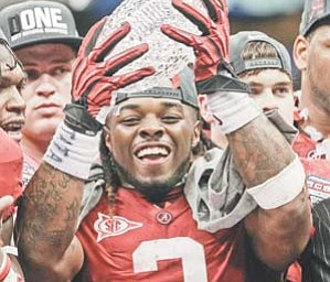 Alabama's Trent Richardson holds up the winning trophy after the BCS National Championship game against LSU