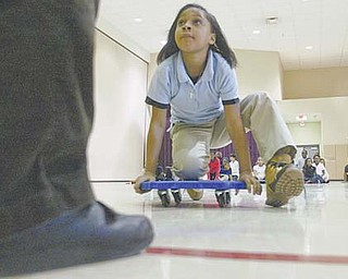 Desiree D'Altorio, a fourth-grader at Taft Elementary School, Youngstown, rolls into the Relay for Learning at the school. Students, divided into teams, race to the front of the gymnasium, answer a question and race back.