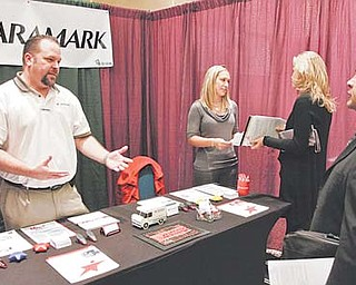 Aramark service managers Randy Nelson, left, and Brittany Howard, center, talk to job-seekers Tuesday at the HireLive career fair in Los Angeles. More people sought unemployment benefits last week as companies let go of thousands of workers hired for the holiday season.