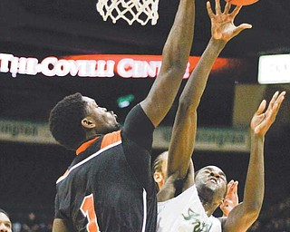 Ursuline's Kevin Jackson (30) has a shot blocked by Sharon's Marlin Sanders (1) in the third period of their basketball game during the See Them Rise Classic on Monday at the Covelli Centre in Youngstown. The Irish edged the Tigers, 57-55.