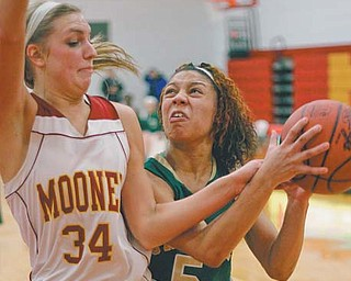 Aurielle Irizzary (5) of Ursuline attempts to drive past Cardinal Mooney's Taylor Woytek (34) during the second period of their basketball game Thursday at Cardinal Mooney High School. The Irish defeated the Cardinals, 38-28.
