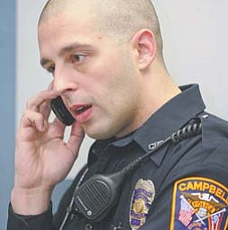 Campbell Officer Eric Manning makes a call on a cellphone at the police station. The city building, including police and fire departments, lost landline service Wednesday night and still was without it Thursday. Also  affected were 2,500 other customers in the city. Police and fire department calls on their main numbers were rerouted to cellphones. 911 service was being dispatched by Mahoning County to Campbell through radios and remained unaffected.
