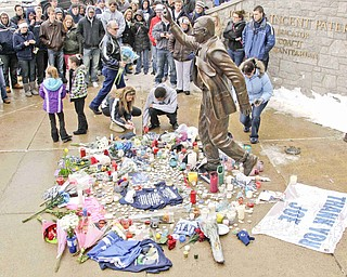 Penn State fans pay thier respects at a statue of Joe Paterno outside Beaver Stadium on the Penn State University campus after learning of his death Sunday, Jan. 22, 2012 in State College,Pa.. (AP Photo/Gene J. Puskar)