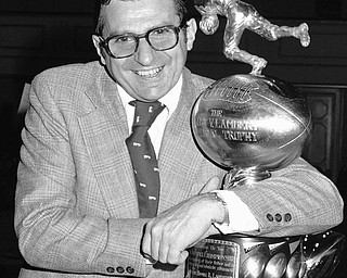 Joe Paterno, head coach of the Penn State Football Team, clutches the Lambert Trophy in New York on Dec. 6, 1973 after it was awarded to his team as emblematic of collegiate grid supremacy in the east. (AP Photo/Dave Pickoff)