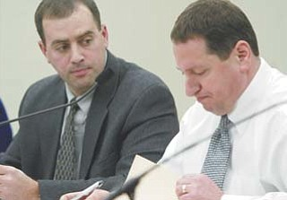 Liberty Board of Education President Joe Nohra, right, reads a list of more than $1 million in cuts to district personnel as board Vice President David Malone looks on. The cuts will go into effect at the beginning of fiscal year 2013, which begins July 1.