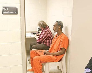 Mahoning County Deputy Sheriff Stephanie Harchar stands guard as Artis Walton is video-arraigned from the county jail on a criminal-trespass charge. Brenda Rider, sitting next to Walton, is a Youngstown Municipal Court bailiff who took notes. Walton, who pleaded innocent, was one of seven inmates to be video-arraigned Monday.